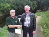 Tommy McGrath competition secretary of Moyola Angling Association presents a cheque for £1240 to John Barry of Cancer  Research UK Castledawson branch