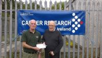 Tommy McGrath presents a cheque for £315 to William Quigley of Cancer research N I.